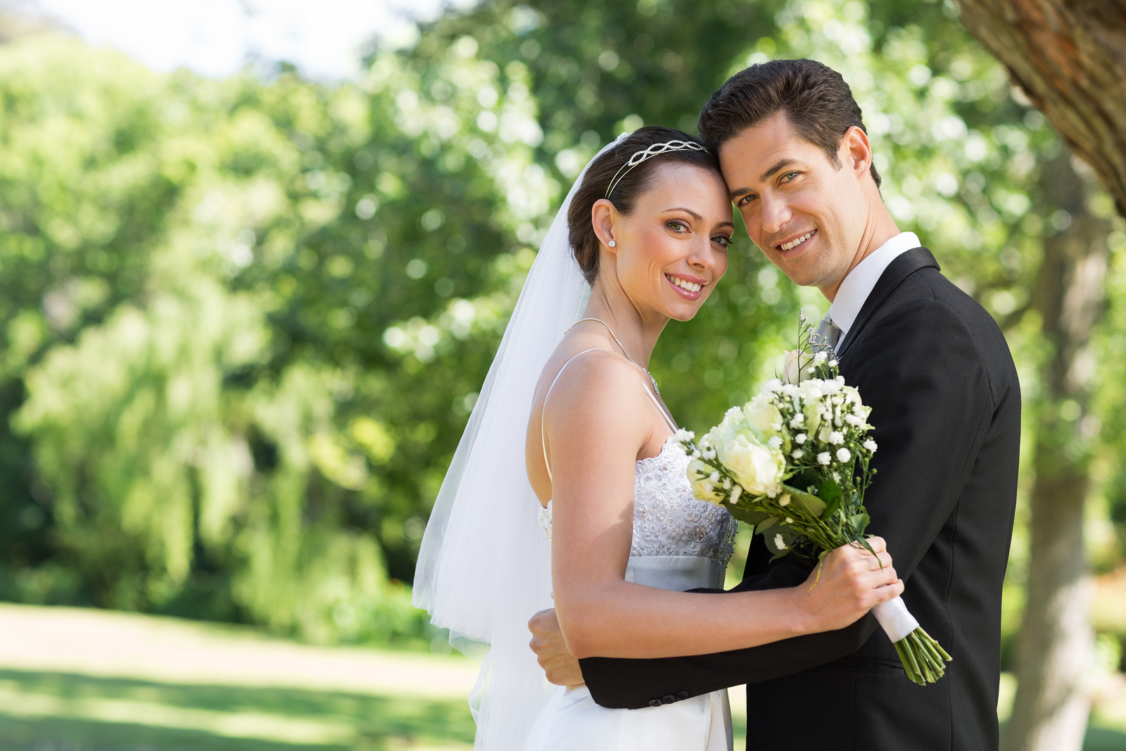 Portrait of loving newly wed couple with head to head standing i
